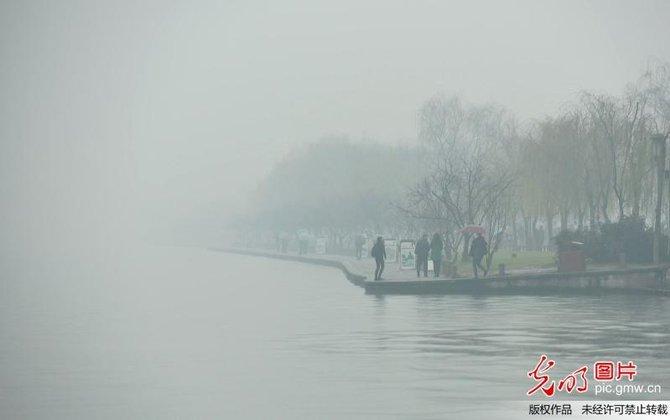 月4日,浙江省杭州市,游客行走在雾霾笼罩的杭州西湖白堤上.-雾