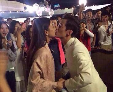 照片中,何炅穿着一件白色中山装,赵丽颖穿着白色旗袍,两人手牵手亲吻图片